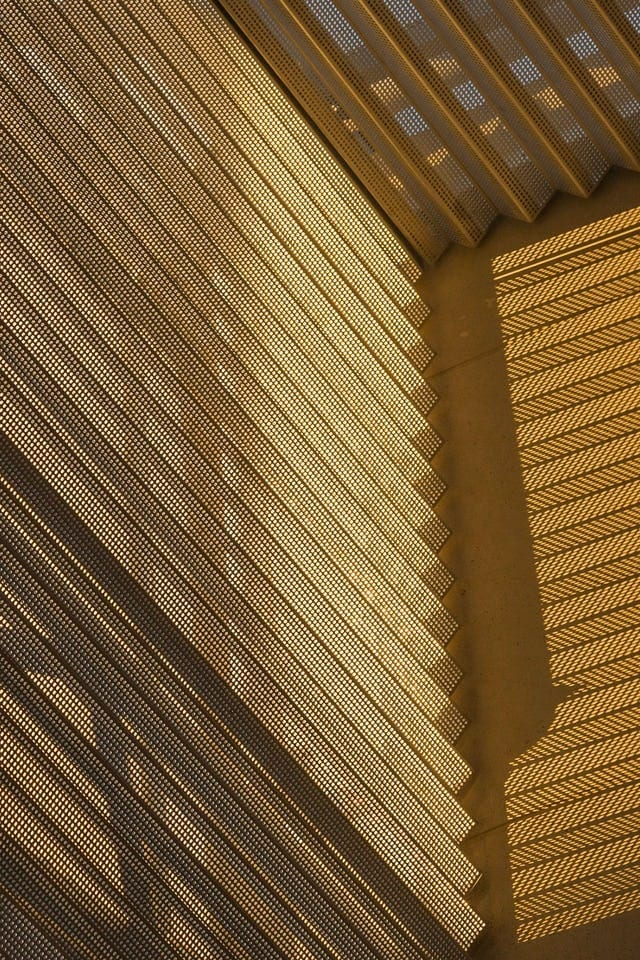 DETAIL OF CORRUGATED PERFORATIONS AND CAST SHADOWS.