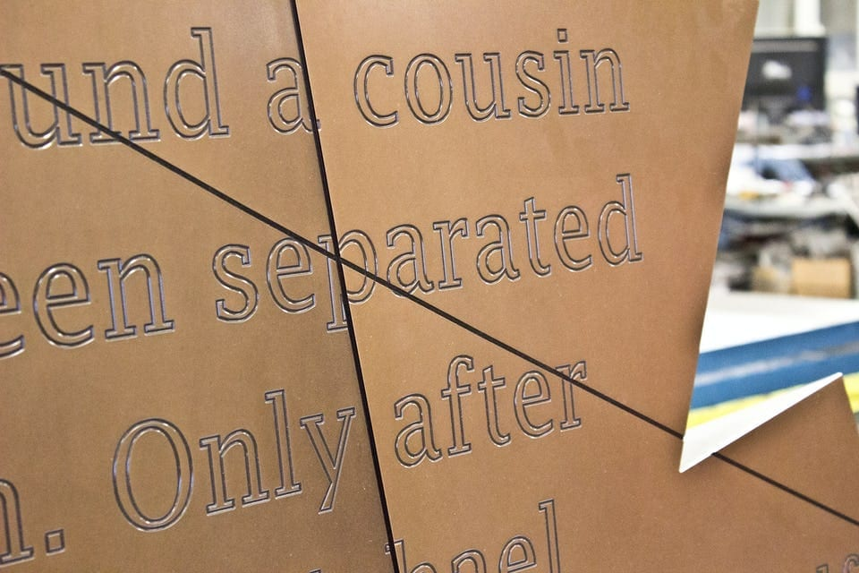 CUSTOM ENGRAVED LETTERING ON PATINATED BRONZE.