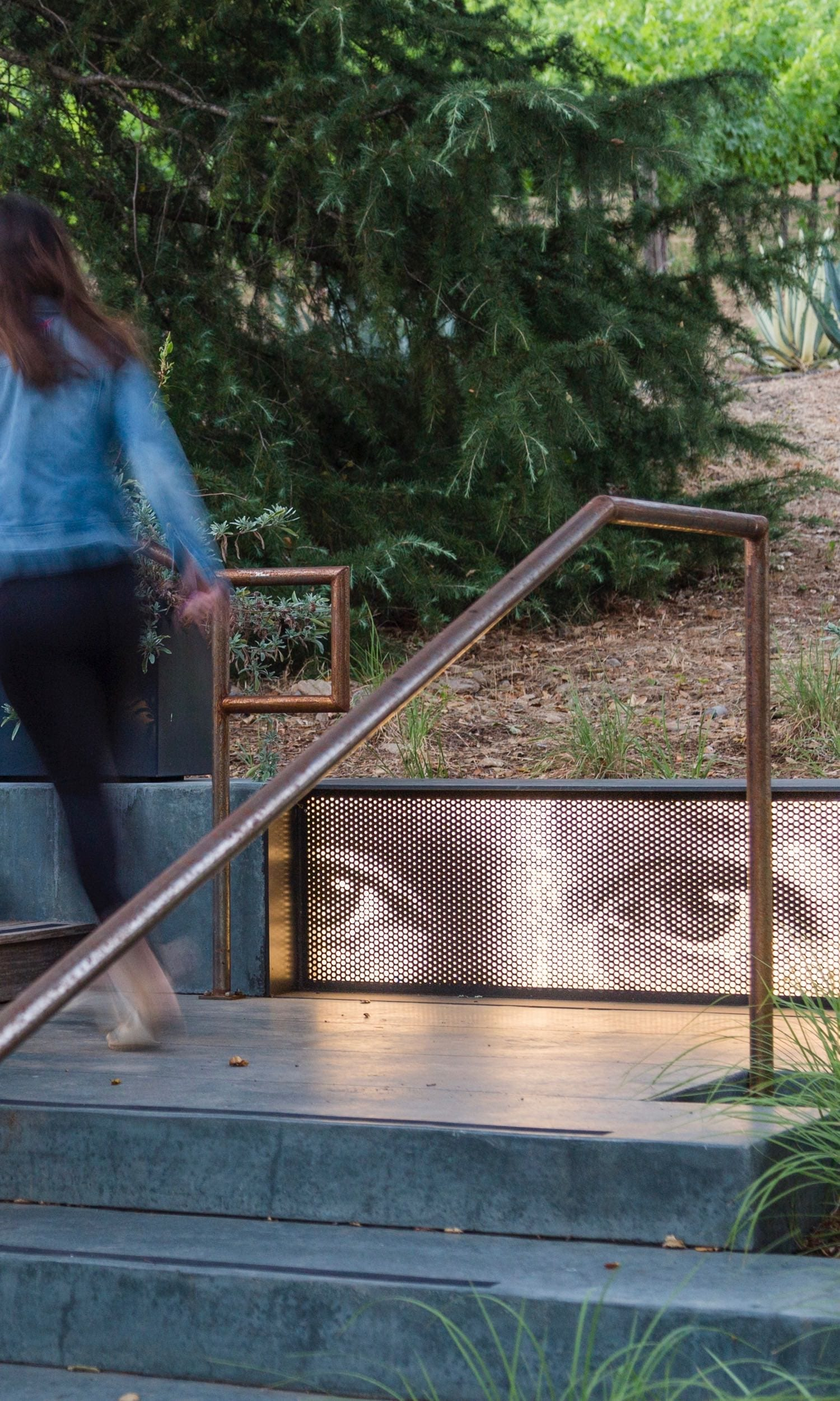 Backlit, finely perforated painted aluminum panel forms the front of a metal seat.