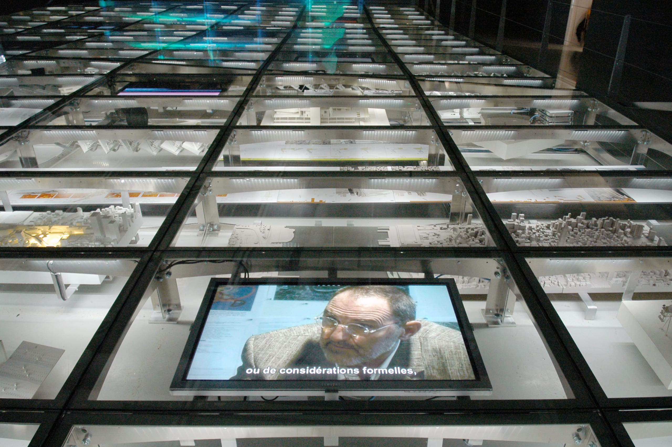 Video screens show Thom Mayne of Morphosis underneath the glass flooring.