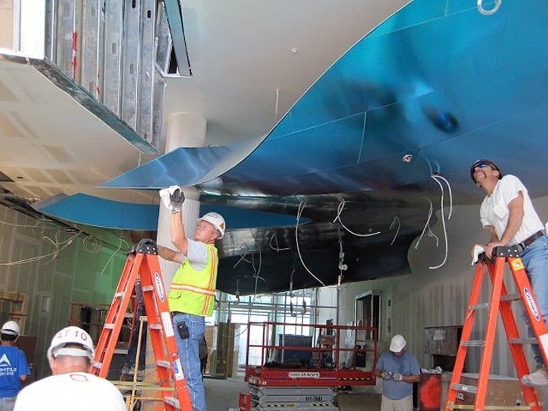 Zahner installers finish the titanium edges.