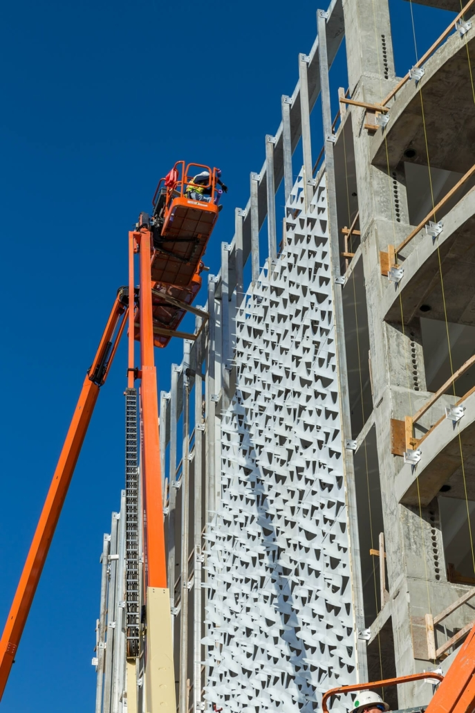 Photo of installers hanging wrapped panels for the Leong Leong facade