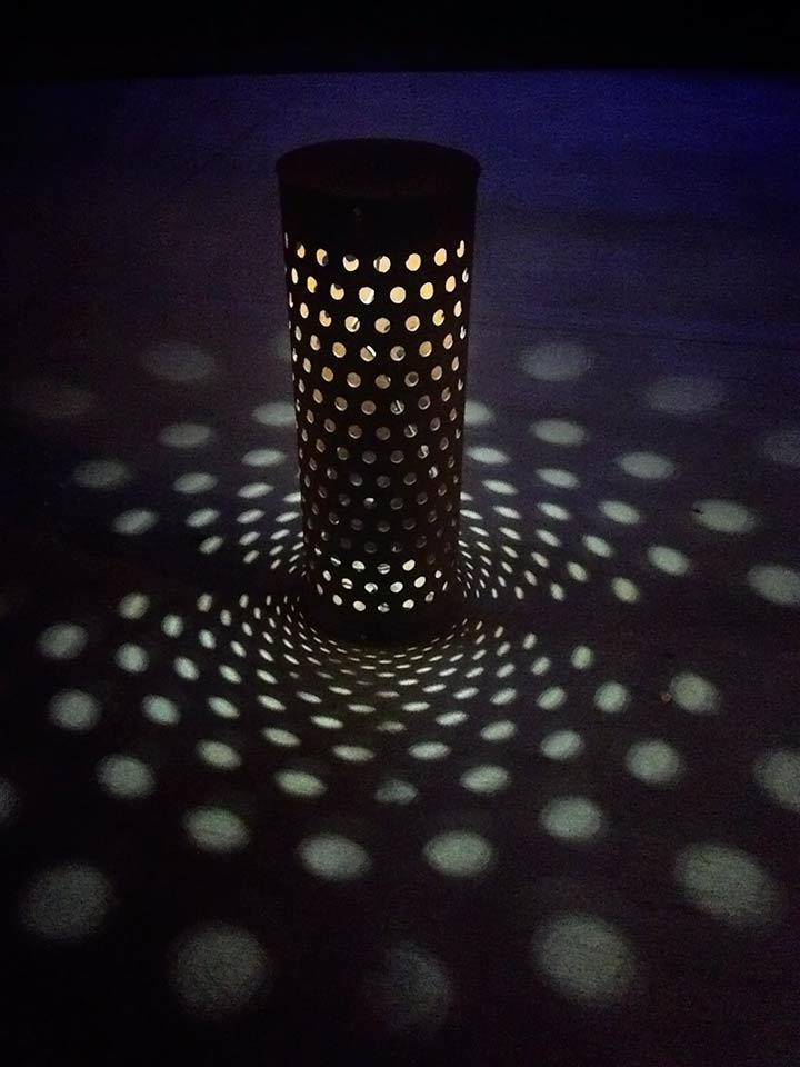 Custom cylinder sidewalk lights cast unique shadows through perforations.
