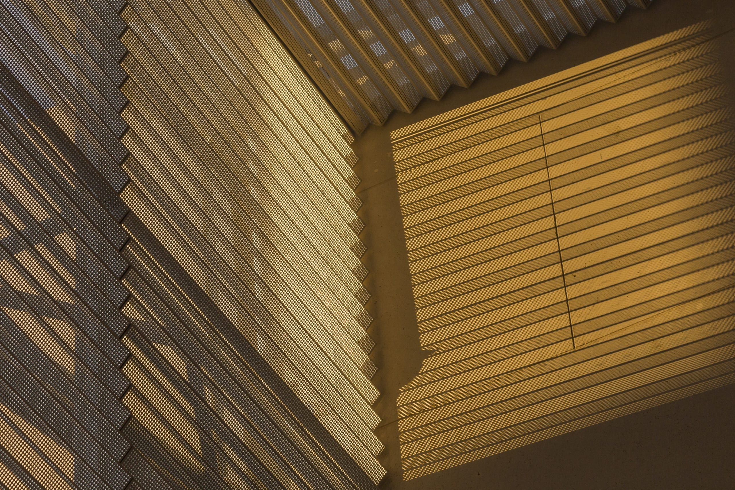 Detail of the argyle shadows cast by folded metal with perforations.