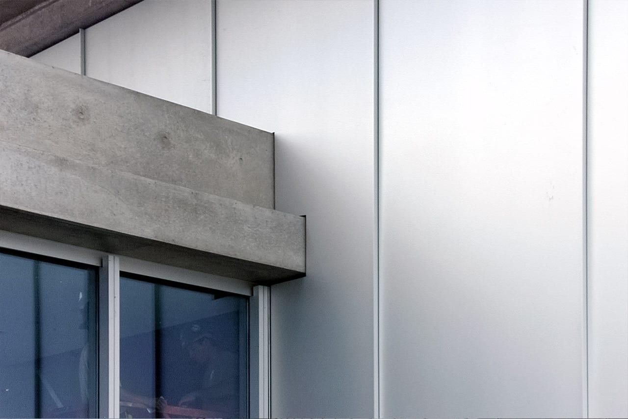 Custom metal details where aluminum wall panels meet concrete slab