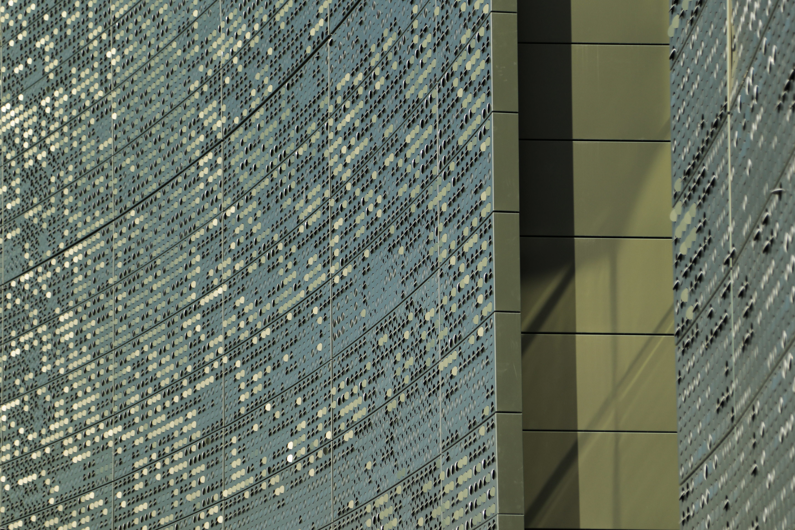 Detail of the louvered perforation patterns on color-shift iridescent painted aluminum panels.