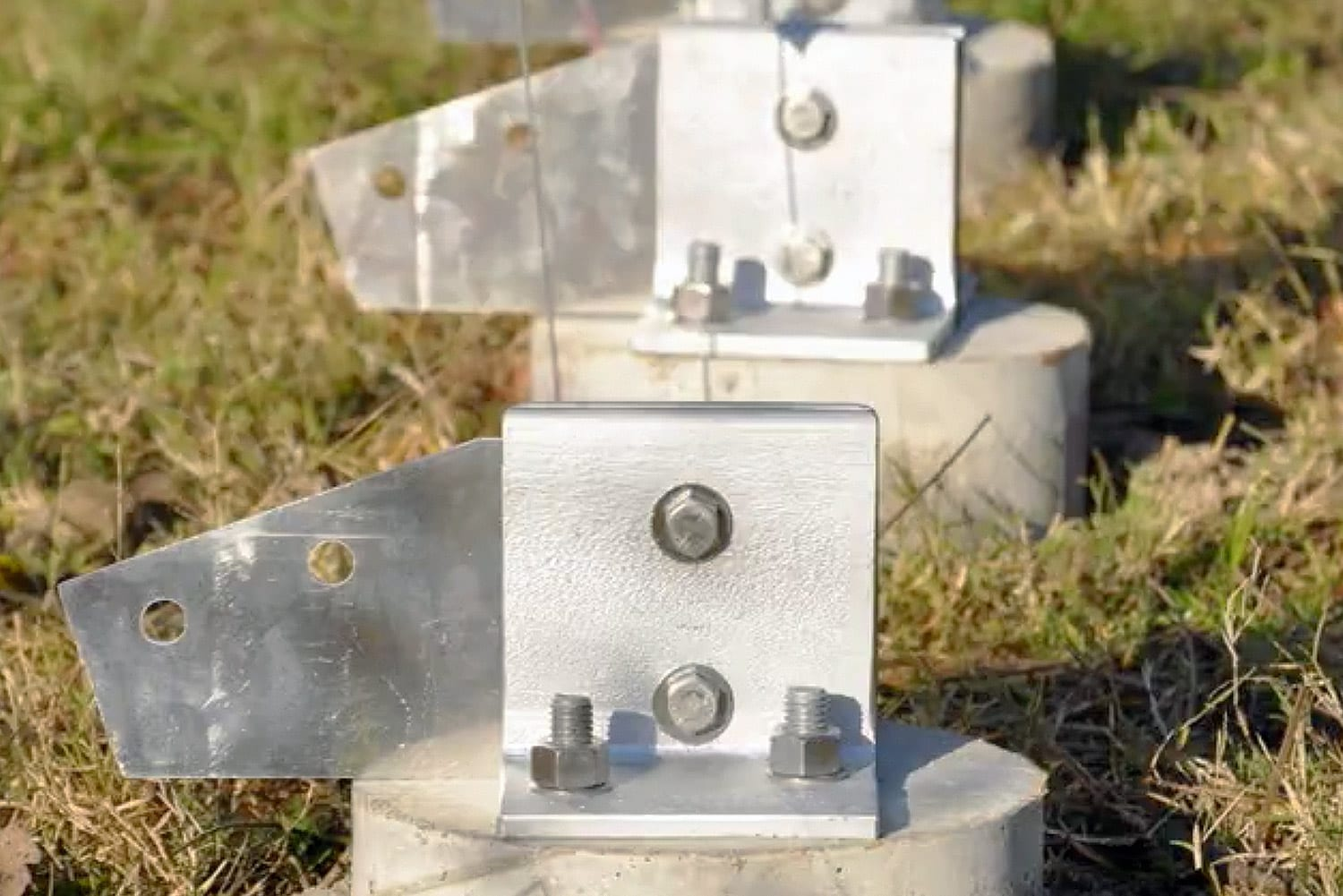 Custom aluminum connections are fastened to concrete footings.
