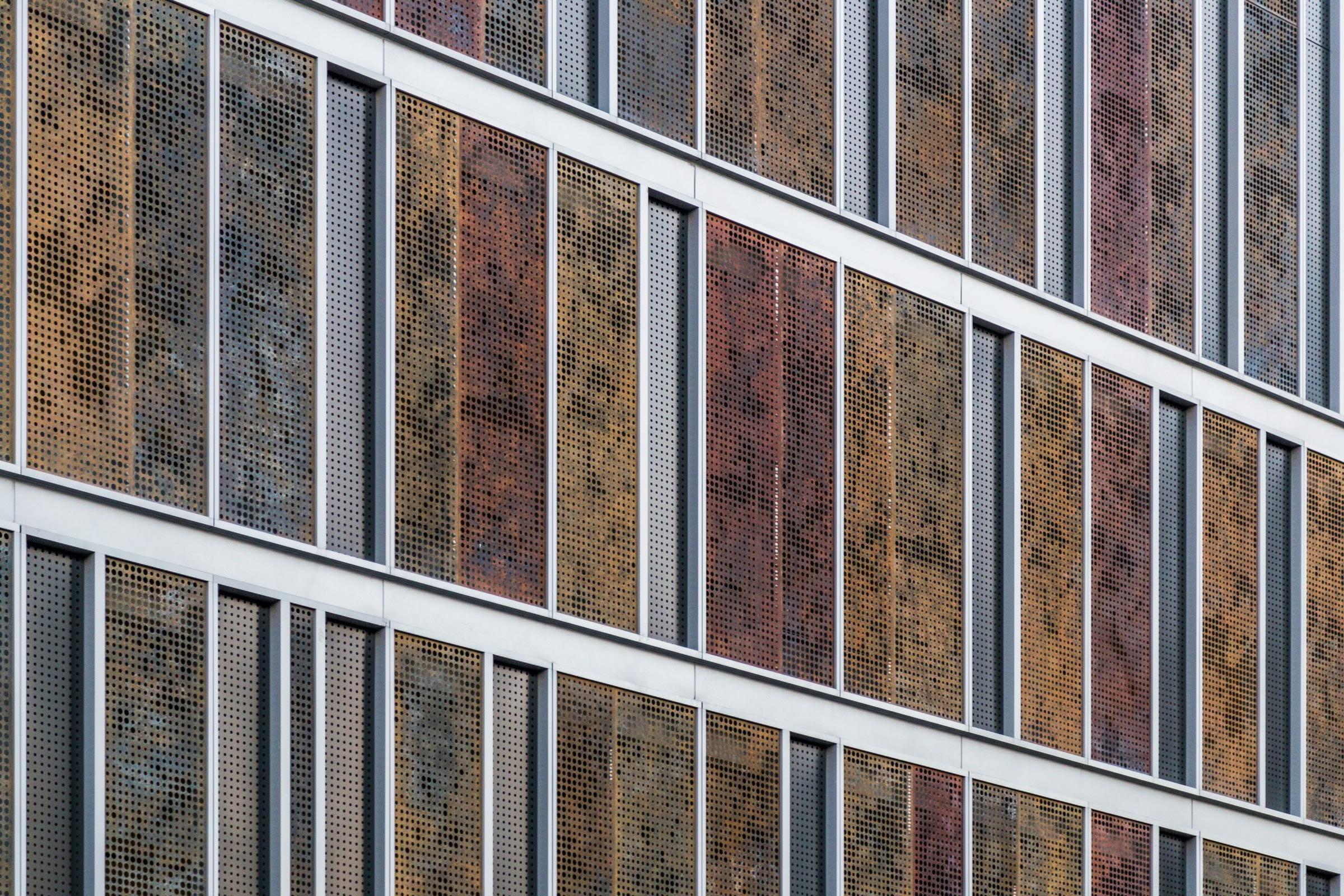 Custom patinated zinc and aluminum panels adorn the parking facade for Children's Hospital Richmond Pavilion.