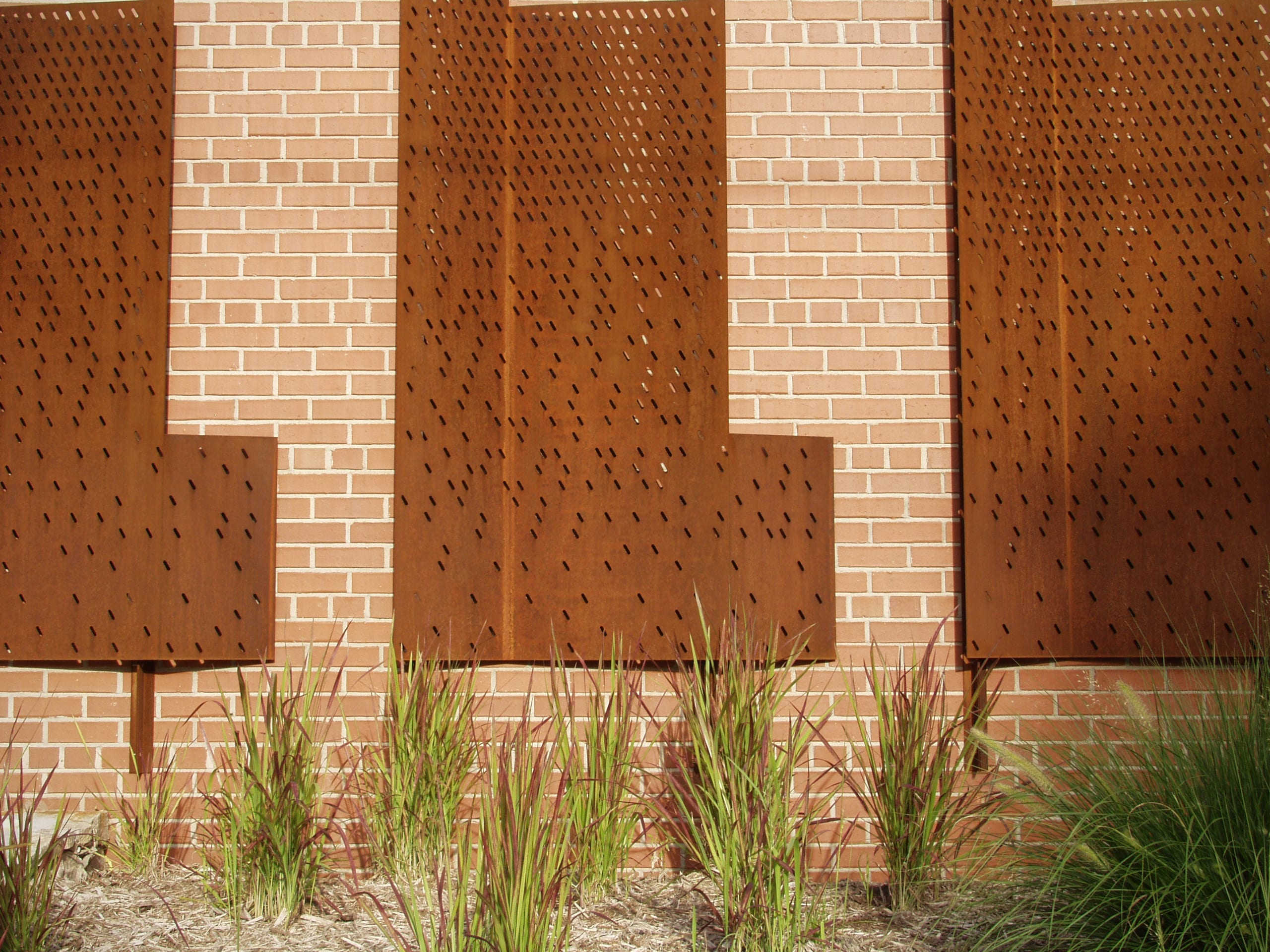 The perforated metal gate motif continues onto the brick wall as an wall-mounted metal artwork.