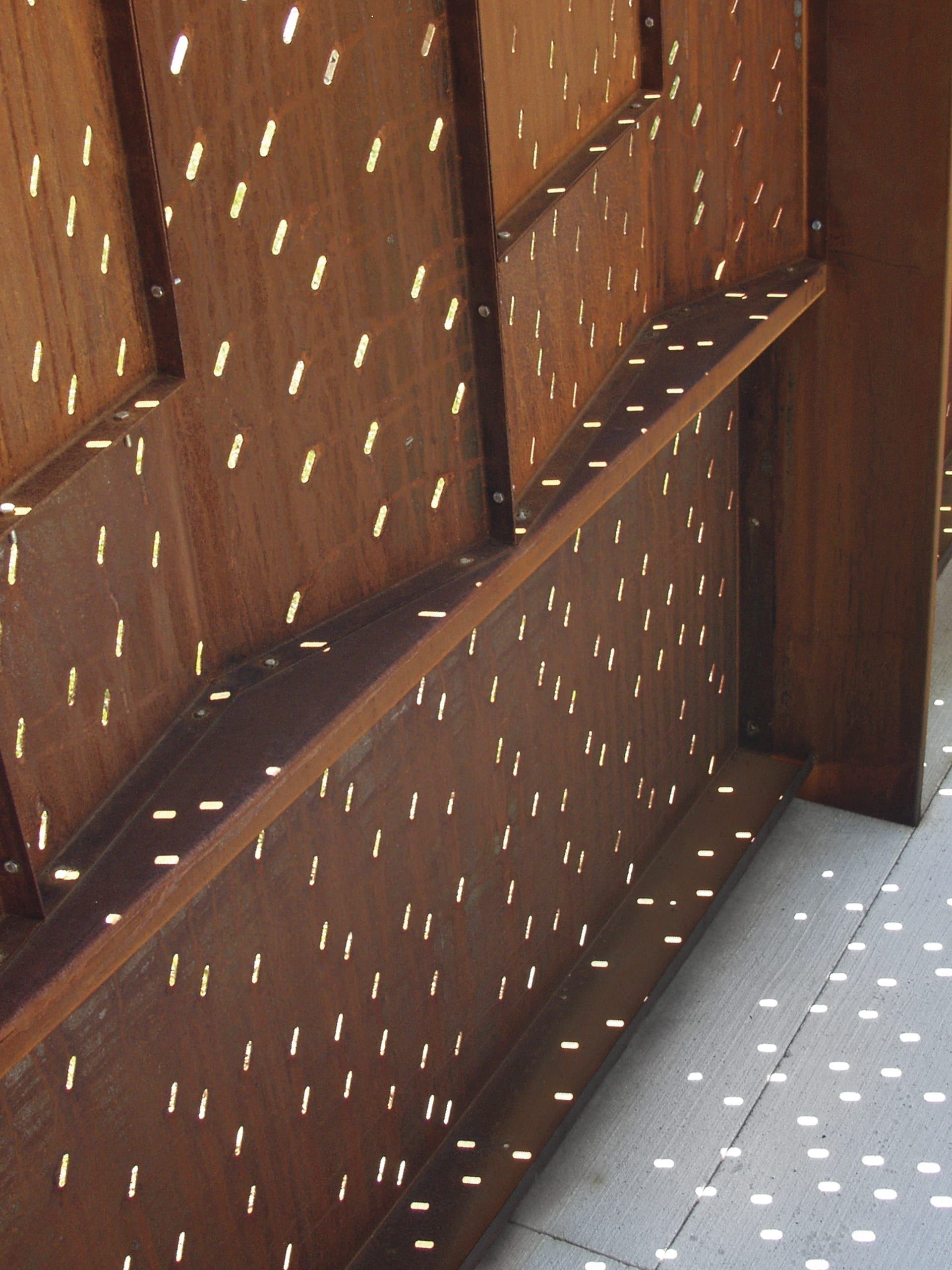 Custom obround die-shapes were used to create the oval perforation patterns in the weathering steel.