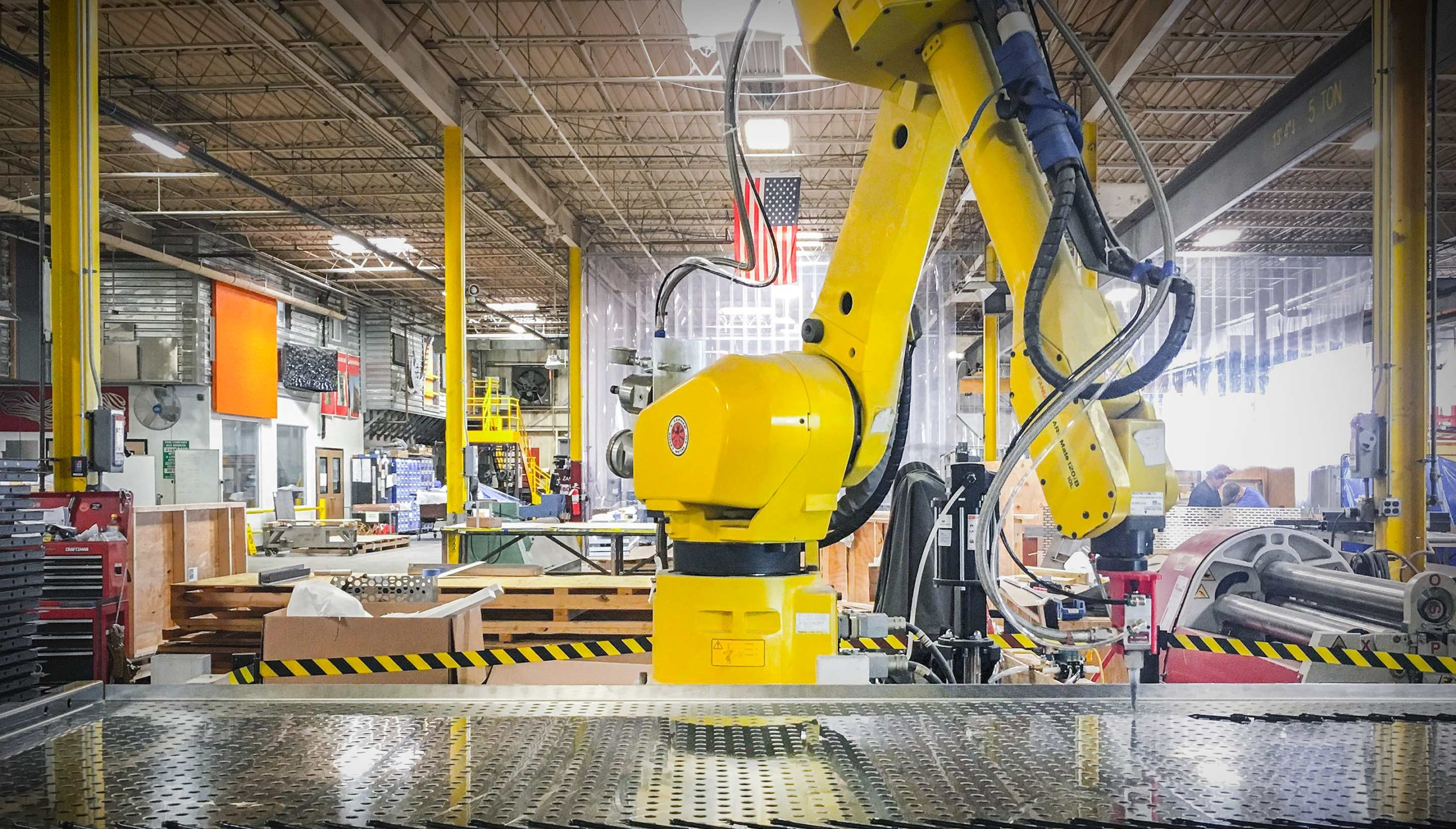 Zahner shop robotic arm places adhesive on perforated metal panels.
