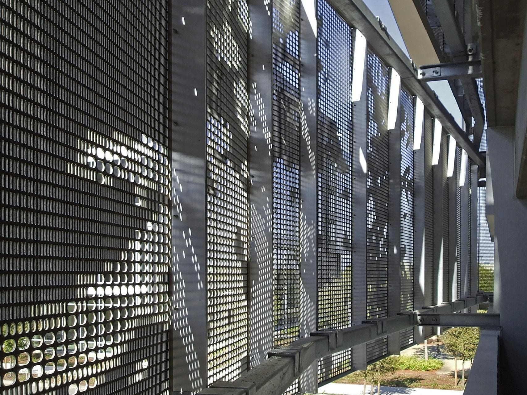 Detail of the undulating facade design by WRNS Studio with custom oval perforation design.