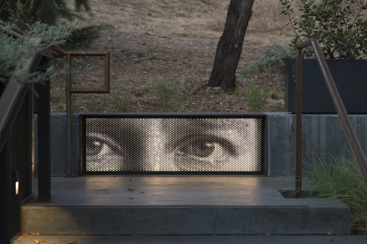 Backlit, finely perforated painted aluminum panel which forms the front of a metal seat.