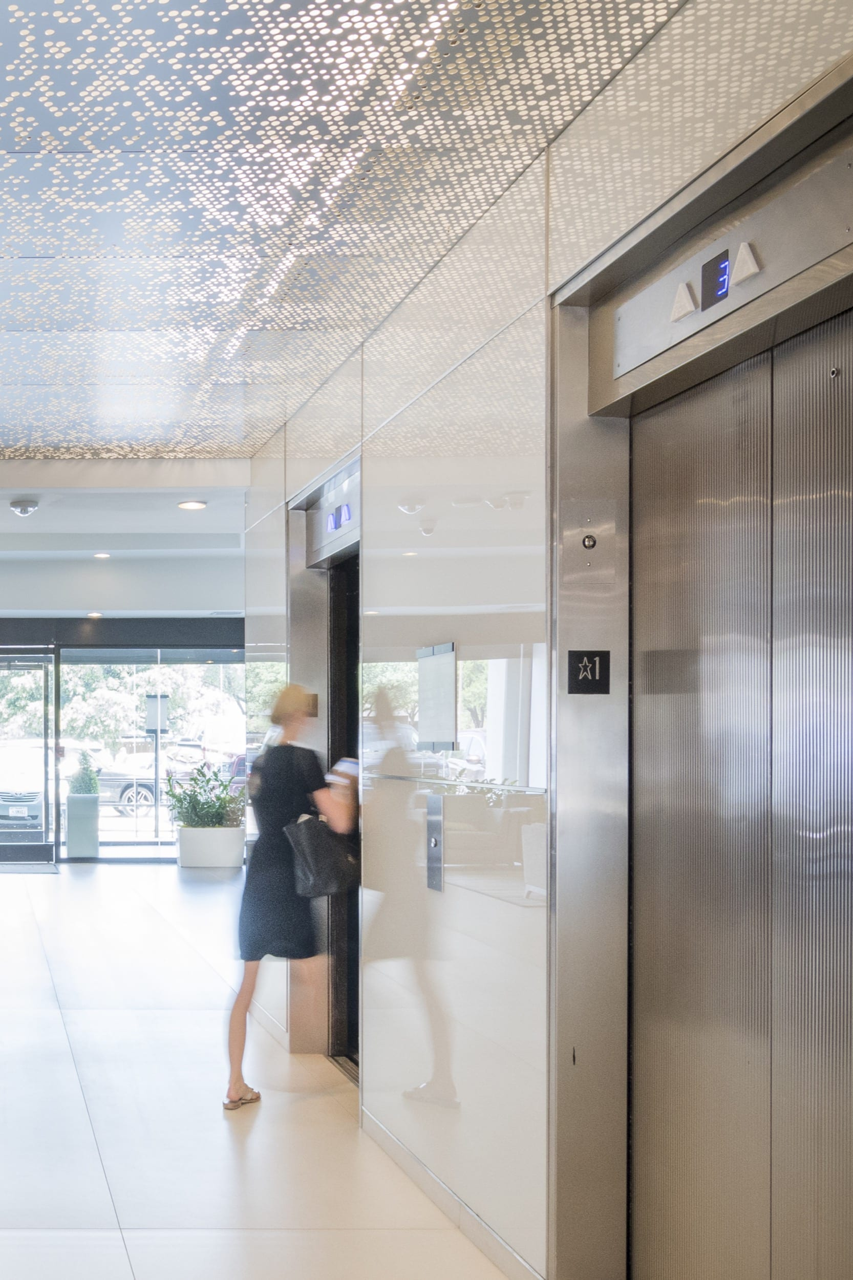 Woman enters an elevator below an ImageWall ceiling.