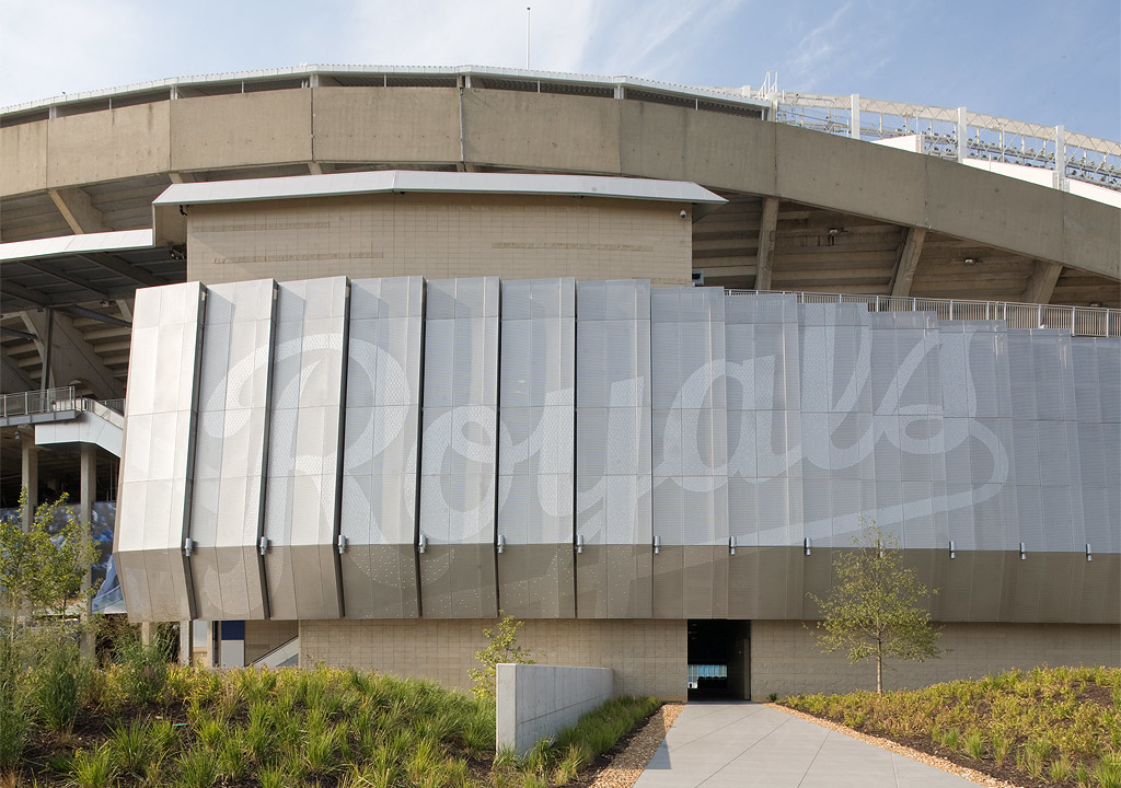 """Kauffman stadium facade with perforated """"Royals"""" logo emblazoned on its wall."""
