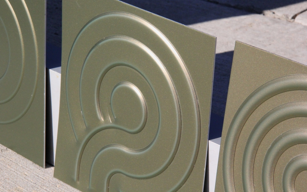 Embossed panel with offset wheel in color shifting coil coated aluminum