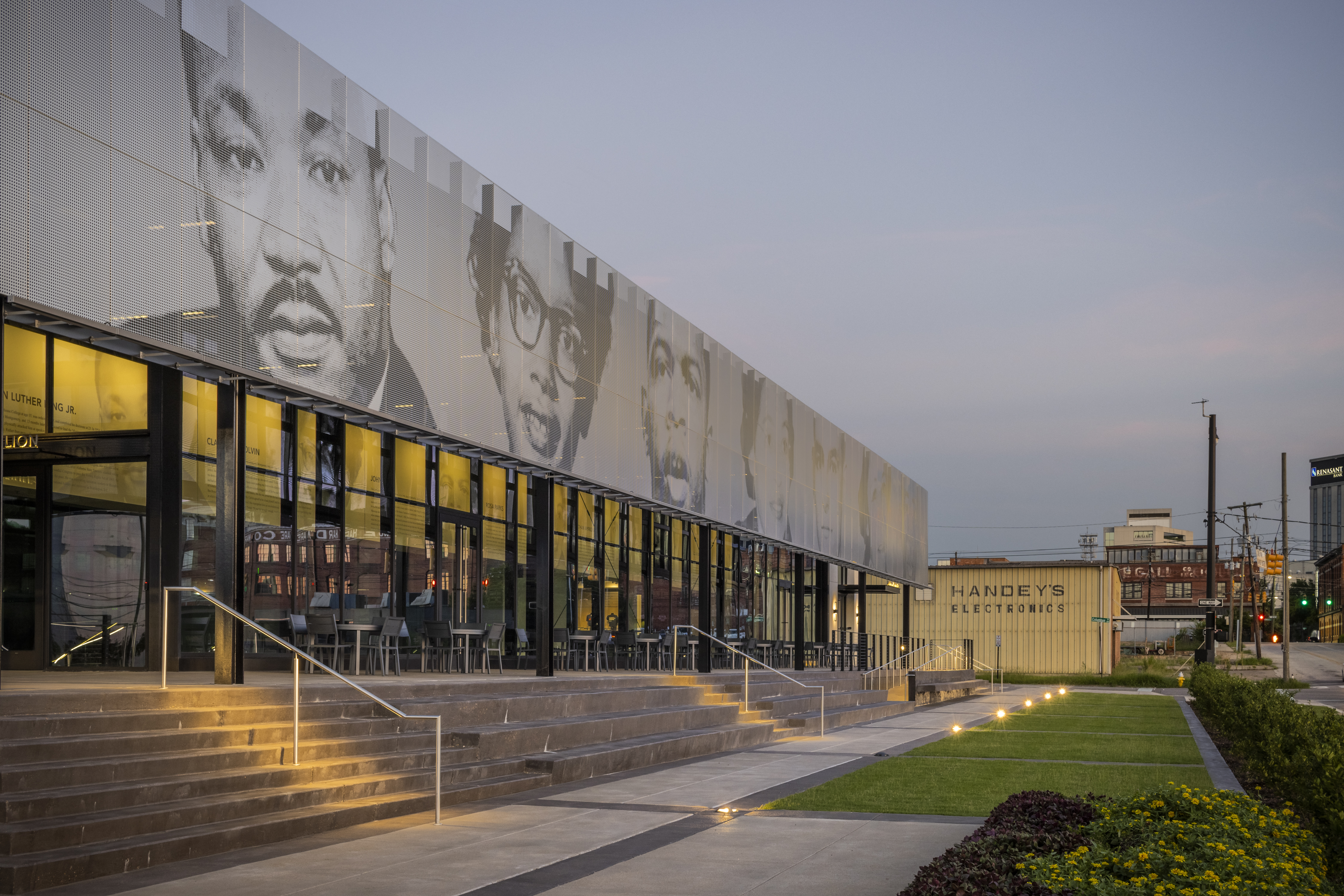The iconic figures depicted on the EJI Legacy Pavilion ImageWall include Martin Luther King Jr., Claudette Colvin, John Lewis, Rosa Parks, Jonathan Daniels, Jo Ann Robinson, and E.D.